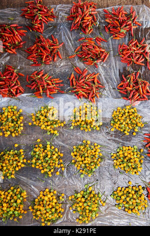 Portions of red chillies and yellow amazonian fruit being sold in Belem Market, Iquitos, Peru. - Stock Image