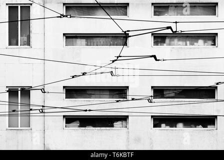 Tram overhead electrical wires in front of a building facade, Milan, Italy - Stock Image