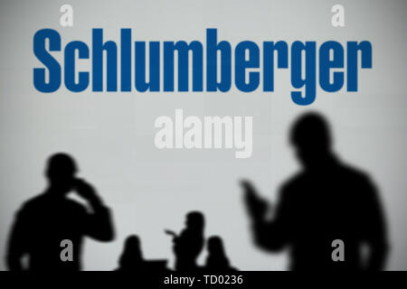 The Schlumberger logo is seen on an LED screen in the background while a silhouetted person uses a smartphone in the foreground (Editorial use only) - Stock Image
