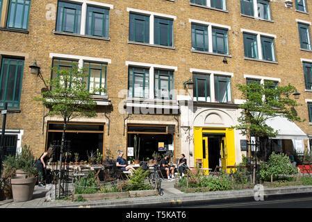People siting outside Cafe Oto, Dalston London Borugh of Hackney - Stock Image
