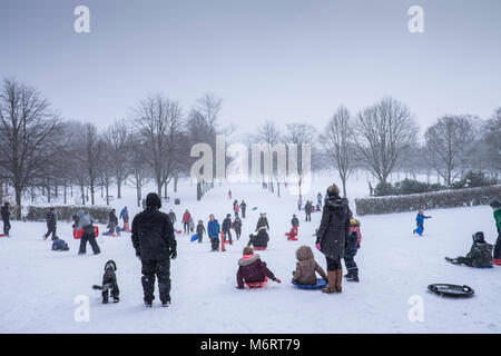 People sledging and enjoying the snow in Glasgow's Victoria park. - Stock Image