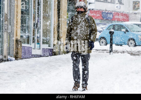 Chippenham, Wiltshire, UK. 1st February, 2019. A man is pictured as he braves heavy snow showers in Chippenham town centre. Credit: Lynchpics/Alamy Live News - Stock Image