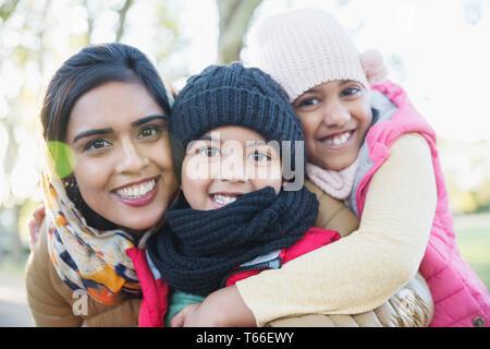 Portrait happy mother and children hugging - Stock Image