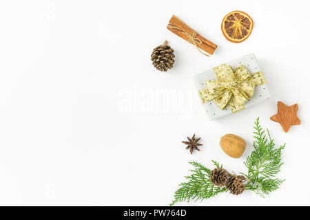 Gift box wrapped in silver polka dot paper golden ribbon bow pine cones juniper nuts cinnamon on solid white background. New Year presents holiday pre - Stock Image