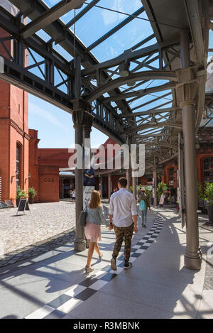 Poland shopping centre center, rear view of young people approaching the entrance to the Stary Browar shopping mall in the city of Poznan, Poland. - Stock Image