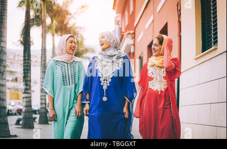 Happy Muslim women walking in the city center - Arabian young girls having fun spending time and laughing together outdoor - Stock Image