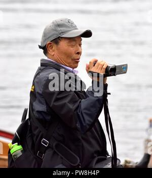 Tourist using a Sony Handycam video camera,Bowness On Windermere,Lake District,Cumbria,England,UK - Stock Image