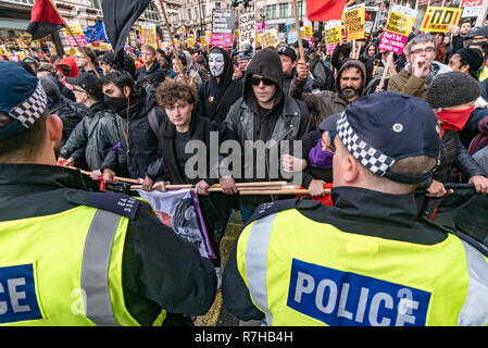 London, UK. 9th Dec, 2018. A line of anti-fascists goes to the front of the protest as police bring the march to a halt because there are hooligans trying to disrupt it. The marchwas a united counter demonstration by anti-fascists marches in opposition to Tommy Robinson's fascist pro-Brexit march. Police had issued conditions on both events designed to keep the two groups well apart. Credit: Peter Marshall/Alamy Live News - Stock Image