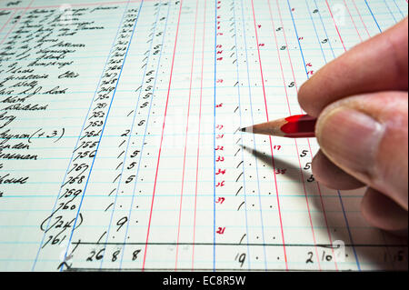 Close up of an accountant checking the figures in an old hand-written bookkeeping ledger. Sums in pounds shillings - Stock Image