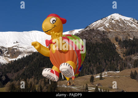a Cameron SS-120 Turtle special shape hot-air balloon flying with trees, snow and mountains behind - Stock Image