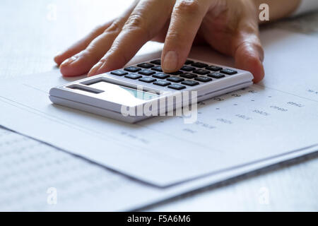 Analyzing numbers and doing calculations at the office - Stock Image