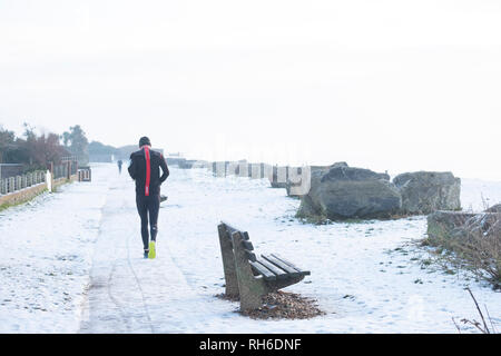 Ferring west Sussex, UK. Friday 1 st Febuary. UK weather. After moderate snowfall last night Ferring wakes to snow covered beaches and this runner braves the elements. Credit: Photovision Images News/Alamy Live News - Stock Image