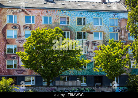 Facade design, on a building in Dusseldorf, Germany, the Catholic community Flingern, Gerresheimer Strasse, big faces, portraits are painted on the fa - Stock Image
