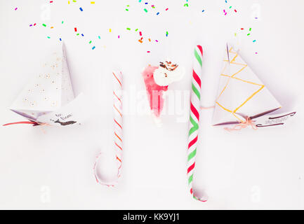 Christmas Decoration with cake slice gift boxes with cake piece and candy canes and confetti falling for best background - Stock Image
