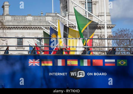 A tour bus with international flags passes larger flags of the Commonwealth that are flying in Parliament Square on the occasion of Commonwealth Day, on 11th March 2019, in London, England. - Stock Image