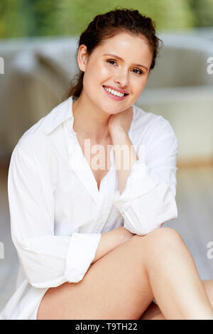Woman sat relaxed smiling - Stock Image