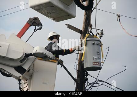 A utility worker repairs a damaged electrical transformer to restore power during relief efforts in the aftermath - Stock Image
