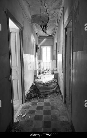 Interior corridor in ruined facilities at the abandoned Canfranc International railway station (Canfranc, Pyrenees, Huesca, Aragon, Spain).B&W version - Stock Image