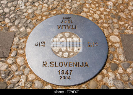 A plaque on the border where there was once a wall in Piazza Della Transalpina, Trg Evrope in Slovenian. The square is divided between Gorizia in Ital - Stock Image