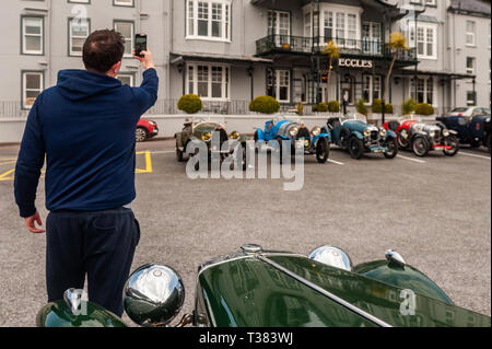 Glengarriff, West Cork, Ireland. 7th Apr, 2019. The French car club 'Amilcar' is currently on a 6 day tour of Ireland.  The club made a stop at the Eccles Hotel, Glengarriff this afternoon. Ian McGregor from Cork took a selfie with a vintage MG. Credit: Andy Gibson/Alamy Live News. - Stock Image