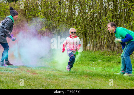 Small boy running hard and being covered in paint on Macmillan cancer charity 5K colour fun run. - Stock Image