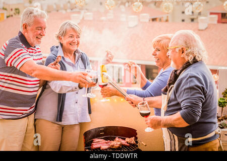 Matures group of elderly people enjoying together a barbecue at home laughing and smiling - happy active retired senior lifestyle - friendship and cel - Stock Image