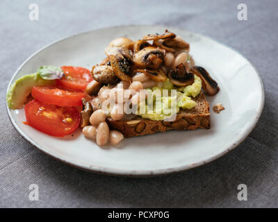 Avocado Toast with White Beans and Mushrooms. - Stock Image