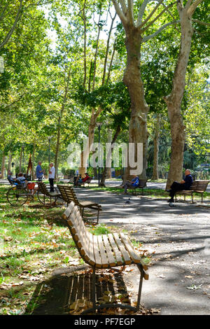 People enjoying and relaxing on a Sunday morning in the sun at the park. Piacenza, Italy, Europe. - Stock Image