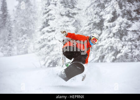 Snowboarder jumps backcountry freeride off-piste ski resort - Stock Image