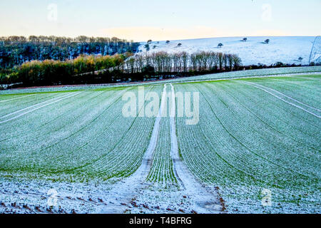 freshly ploughed field covered in a thin layer of white frost forming vertical lines, the field is on a hill and behind is the rolling countryside of  - Stock Image