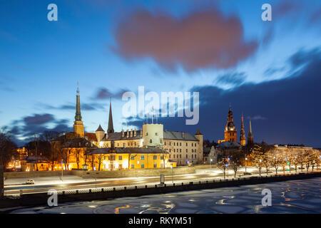 Winter dawn in Riga old town seen across frozen Daugava river. - Stock Image