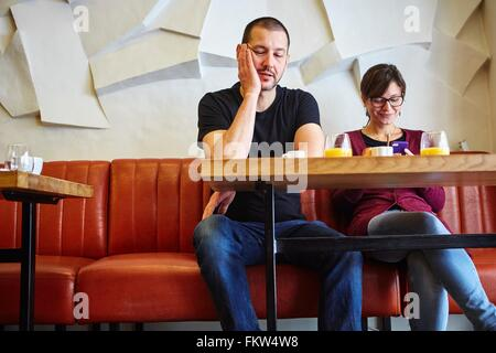 Bored man with girlfriend reading smartphone text in restaurant - Stock Image