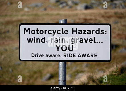 Warning road sign. 'Motorcycle Hazards: wind, rain, gravel...YOU Drive aware. RIDE AWARE.'   Kirkstone Pass, Cumbria, England, United Kingdom, Europe. - Stock Image