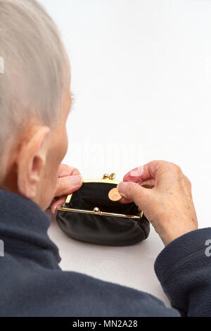 Senior woman holding an empty purse and a two Cent coin in her hands., copy or text space, old-age poverty concept - Stock Image