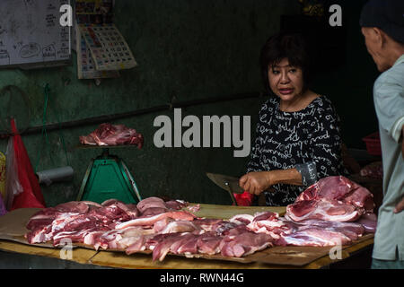 Butcher and customer chatting as raw meat is prepared in an open air low hygiene setting, Melaka, Malaysia. - Stock Image