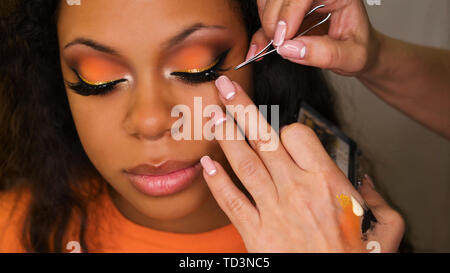 Makeup artist sticks false eyelashes of african american girl. Evening make-up. Closeup portrait. - Stock Image