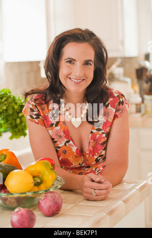 Portrait of a mid adult woman leaning on a kitchen counter and smiling - Stock Image