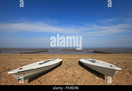 Two sailing boats on the sand at Heacham beach on the Norfolk coast. - Stock Image