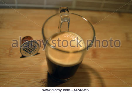 Black coffee in glass on wooden table with used coffee 'pod' next to it. - Stock Image