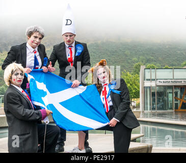 Edinburgh, Scotland, UK. 12th August 2018. Edinburgh Fringe Festival Photocall on a dreary Scottish weather day, Scottish Parliament, Holyrood, Edinburgh, Scotland, United Kingdom. Political clowns in silly poses outside the parliament. Pig Circus is billed as a 'Verbatim Brexit parody' about the government's handling of Brexit negotiations, with characters Teresa May, Boris Johnson, David Davies and Liam Fox holding a saltire, Scotland's National flag. Produced by theatre group Hitchhiker Collective - Stock Image