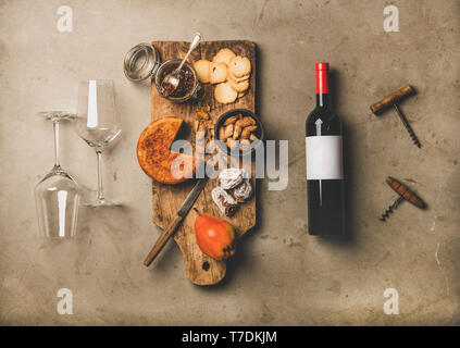Wine and snack set. Flat-lay of wine bottle with blank label, vintage corkscrews, two wineglasses and cheese and appetizers board over concrete backgr - Stock Image