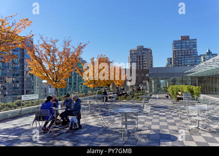 People relaxing and chatting at a table on the Vancouver Public Library rooftop garden that opened on September 29, 2018, Vancouver, BC, Canada - Stock Image