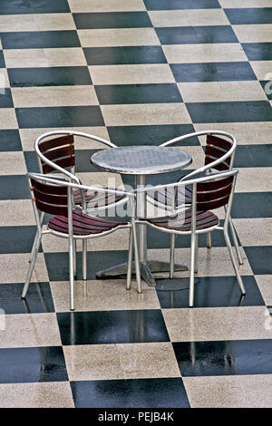 A vacant chrome table and four chairs sit unused on a checkerboard tile floor. - Stock Image
