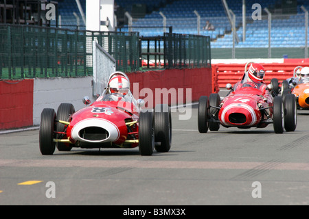 two red racing cars crossing the starting line - Stock Image