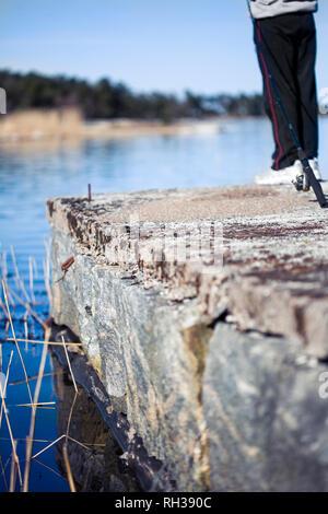 Boy fishing on a concrete jetty - Stock Image