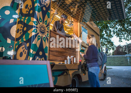 Customer receiving food from vendor at food truck - Stock Image