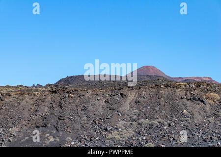 Looking over rocks of lava towards Teneguia Volcano, La Palma Island, The Canaries. Teneguia volcano last erupted in 1971 - Stock Image