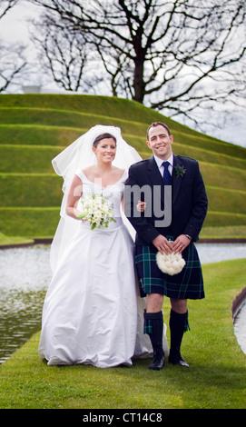 Newlywed couple walking on grassy bridge - Stock Image