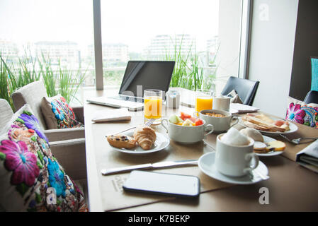 Breakfast and laptop computer on table - Stock Image