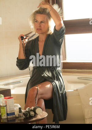 An elegant woman dries her hair after washing it, getting ready to go out for an evening - Stock Image